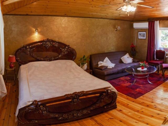 Голяма дървена спалня с допълнителен диван във вила Дияна
